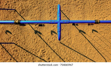 Pole aerial High Dynamic Range (HDR) image of blue playground swings on a sand base. Includes patterns, lines and shadows.