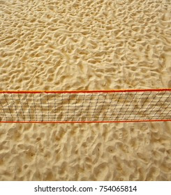 Pole aerial image of a beach volleyball court. Includes an overhead perspective of the net and sand texture.