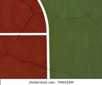 Pole aerial image of an outdoor basketball court. Includes pavement cracks, red key, white lines and green surface.