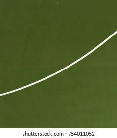 Pole aerial image of an outdoor basketball court. White line intersects green playing surface.