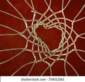 Pole aerial image of an outdoor basketball court. Perpsective shows a heart shape in the bottom of the mesh against a red playing surface.