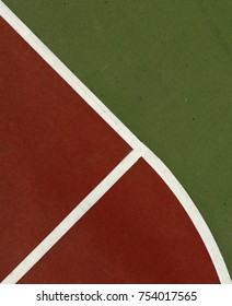 Pole aerial image of an outdoor basketball court. Includes red key, white lines, green surface and triangular shapes.