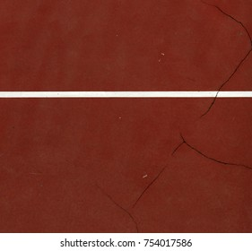 Pole aerial image of an outdoor basketball court. Includes pavement cracks, white line and red surface.