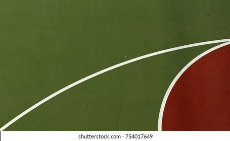Pole aerial image of an outdoor basketball court. Abstract shapes created by red key, white lines and green surface.
