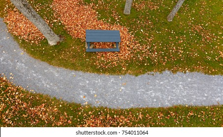 Pole aerial of park walkway with autumn leaves, crushed rock trail, blue picnic table, grass and trees.