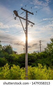 A pole carrying power lines obscures the sun in the early evening.