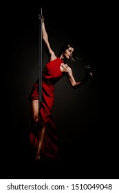 pole dance girl in elegant red outfit holding wine glass posing against dark background
