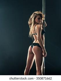 Pole dance. Slim blonde posing with pylon