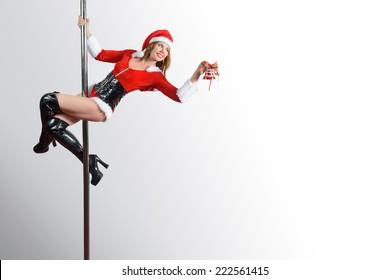 Pole dancer girl as Santa's helper decorating something