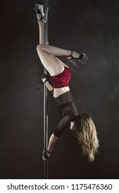 Pole dancer is hanging upside down on the hole and showing trick, on his feet high-heeled shoes.