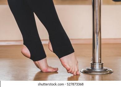 Pole dancer, legs near pylon