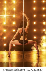 Pole dancing. Sexy woman dancing on a pole