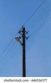 Pole with electric wires against the blue sky