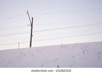 A pole with electrical wires under tension. Winter day, snow.