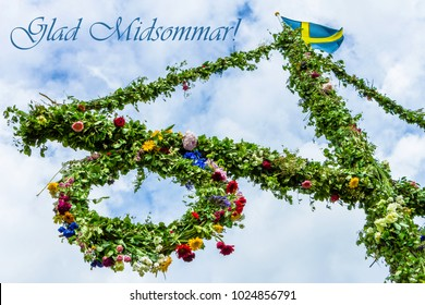 A pole and flag against blue sky and white clouds. A maypole decorated, covered in flowers and leaves. Pole after celebrating midsummer. Midsummer traditional Swedish symbol.  Kort Glad Midsommar.