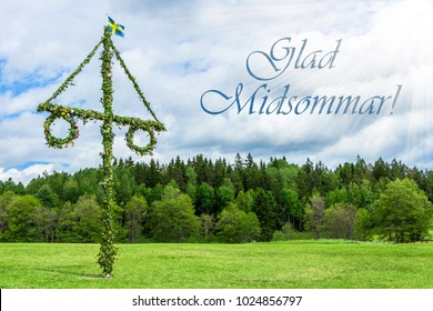 A pole and flag against green trees and blue sky. A maypole decorated, covered in flowers and leaves. Pole in Tyresta National Park. Midsummer traditional Swedish symbol. Kort Glad Midsommar.