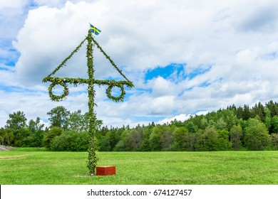 A pole and flag against green trees and blue sky. A maypole decorated, covered in flowers and leaves.