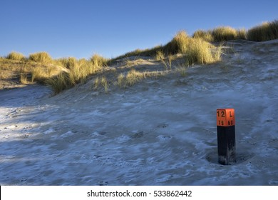 Pole on the frozen North Sea beach near the Dutch village Ouddorp