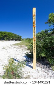 The pole sign implies one mile walking for an hour to the entrance of Little Stirrup Cay tourist island (Bahamas).