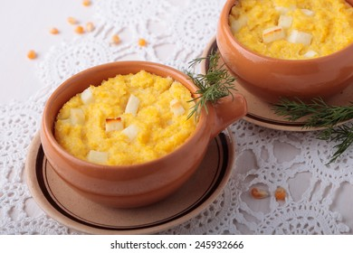 Polenta baked with chunks of cheese in a ceramic bowl