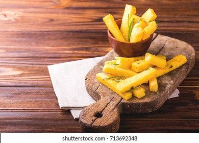Polenta fries with sea salt, parmesan and rosemary. Italian appetizers. Fried corn sticks. Wooden background.  Horizontal view.