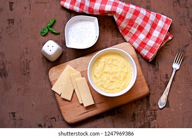 Polenta or hominy, a dish of corn grits or corn flour, in a white bowl on a brown background. Served with sour cream and mint sauce and cheese. Top view.