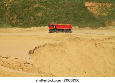 POLEWOJE, KALININGRAD REGION, RUSSIA JUNE 18, 2014: The red dump truck leaves a sandpit