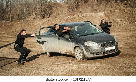 Police agent and bodyguard training action gun shooting from car. Special agent team weapons training and course on outdoor shooting range