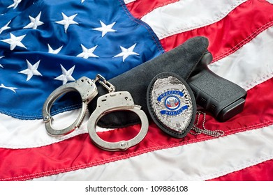 Police badge, gun and handcuffs on an American flag symbolizing law enforcement in the United States.