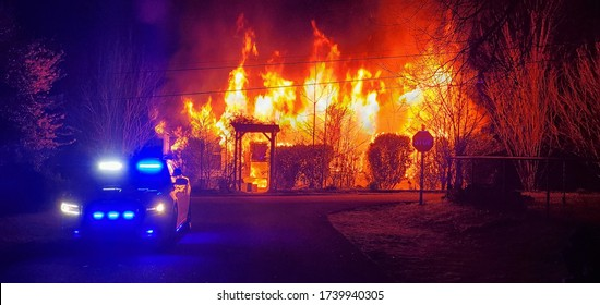 Police begin to shut down a road in preparation for Fire Fighters as a house fire burns. No one was injured.