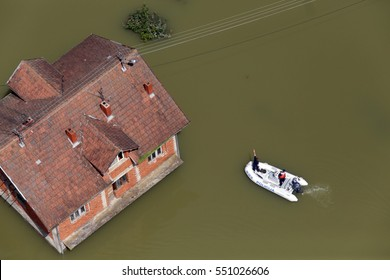 Police in boat oversees flooded house