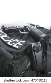 Police body camera on tactical vest for law enforcement with gun in the background