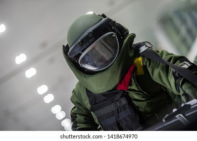 The police in bomb protection suit working in the indoor of airport terminal, to find the bomb.
