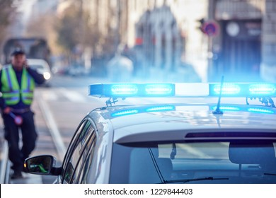 Police car with blue lights on the crime scene in traffic / urban environment.