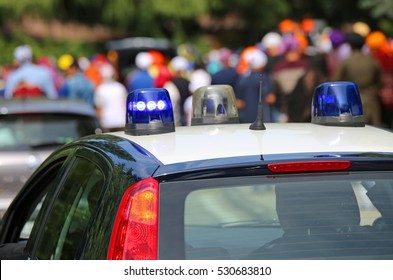police car with blue sirens in the street escorting participants of an event