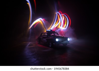 Police car chasing a car at night with fog background. 911 Emergency response police car speeding to scene of crime. Creative decoration. Selective focus