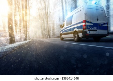 Police car driving through a winter forest.