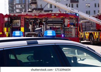 Police car with flashing lights in front of a fire truck.