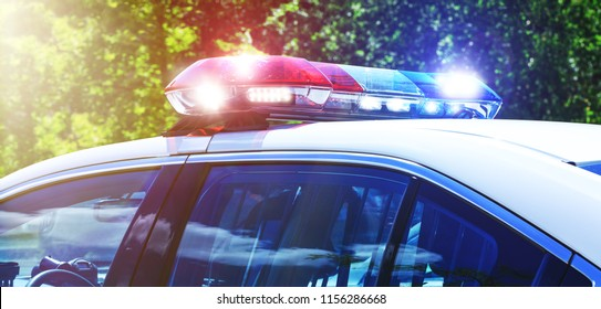 Police car with focus on siren lights. Beautiful siren lights activated in full mission activity. Policemen with patrol car in intervention operation at crime place. Emergency lights flashing.