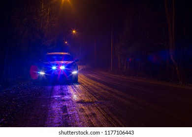 Police car has pulled a car over on a dark and rainy road. Dramatic scene. Horrible weather to drive. Flashing lights. Flare effect applied.