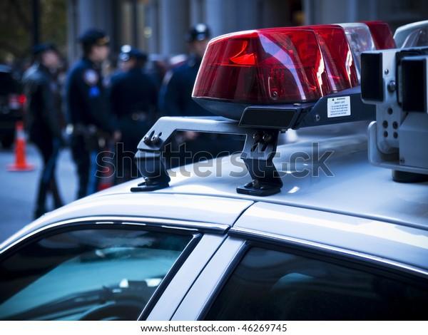 Polizeiauto leuchtet, Nahaufnahme. Eine Gruppe von Polizisten auf dem Hintergrund.