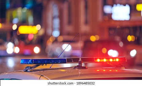 Police car lights at night city street. Red and blue lights. Road traffic accident. Evening patrolling. Motion blur.