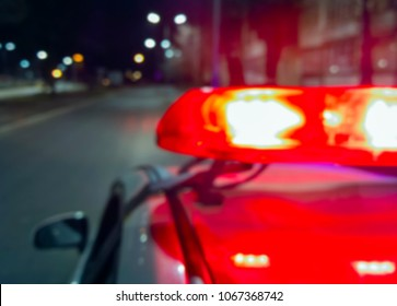 Police car lights in night time, crime scene, night patrolling the city. Abstract blurry image.