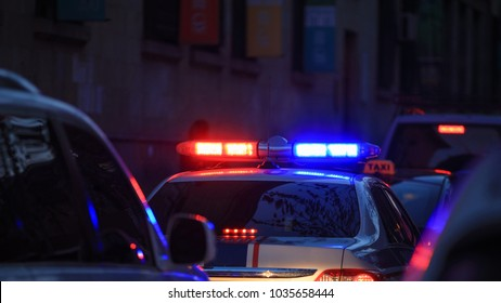 Police car at night with flashing lights.