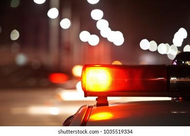 Police car at night, lights flashing in Seoul