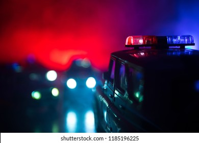 Police cars at night. Police car chasing a car at night with fog background. 911 Emergency response police car speeding to scene of crime. Selective focus