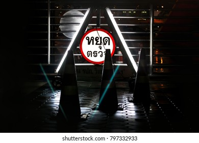 Police check point sign at nigh in Thai language. Stop point to check driver and rider who might over drink and drive, carrying drugs or drive over limit speed