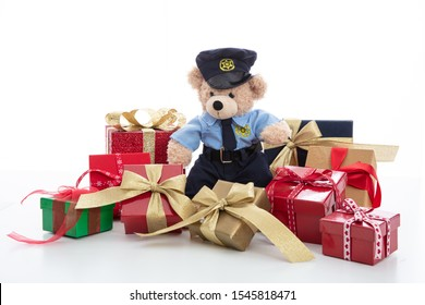 Police and christmas concept. Cute teddy bear in police officer uniform and xmas gift boxes isolated against white background