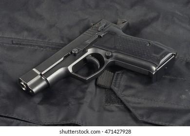 Police concept - handgun on black uniform background