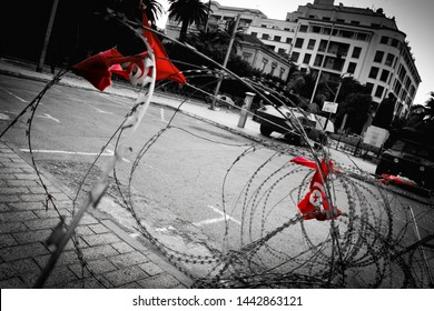 Police control point wire fence on Avenue Bourguiba (Tunis, Tunisia) with blue sky with clouds. Black, white and red